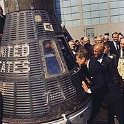 JFK looks at the space craft Friendship 7, the spacecraft which made three earth orbits, piloted by astronaut John Glenn.