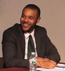 A short-haired man in a black suit and tie smiles and looks to his right, smiling, hands crossed on the table before him.