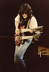 A colour photograph of Jimmy Page performing on stage with a double-necked guitar