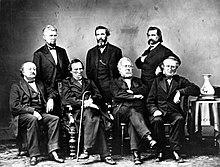 Zeven mannen in kostuums poseren voor een groepsfoto.