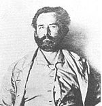 Grainy black and white photograph showing the face and torso of an about 50-year-old bearded man looking into the camera. He is wearing a jacket, and collared shirt that appears to be buttoned only at the top.