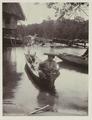 KITLV - 26474 - Kurkdjian - Soerabaja - Woman with child in a small boat near a river bank - circa 1905.tif