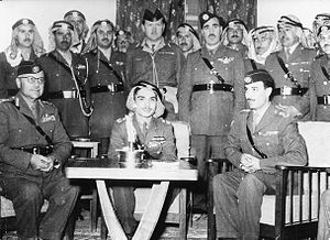 Ali Abu Nuwar - Aide-de-camp Abu Nuwar (seated right) with King Hussein (seated center) and Chief of Staff Glubb Pasha (seated left) with Arab Legion officers standing behind them, late 1955 or early 1956