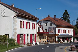 La Cure - Hotel Arbez in La Cure.  The border runs lengthwise through the two buildings, passing just to the left of the mural.  The mural and everything to the right of it lies in Switzerland; France lies to the left.
