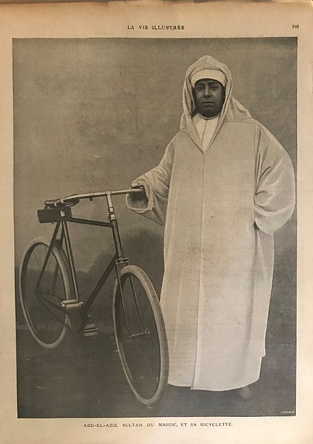 Sultan Abd-el-Aziz with his bicycle in 1901. The young sultan was noted for his capricious spending habits, which exacerbated a major trade deficit.[7]