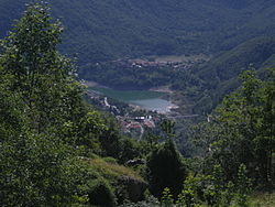 a small lake in a deep wooded valley