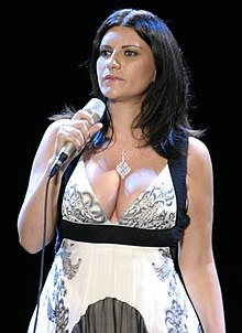 A woman holding a microphone up to his neck in a white dress with black.