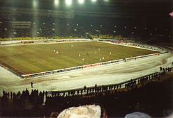 Football match with snow covering the stadium lanes and spectators wearing winter gear
