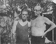 Two middle-aged man pose for an informal photo under some trees. Their arms are behind one another's backs. One man is wearing a t-shirt and the other is bare-chested