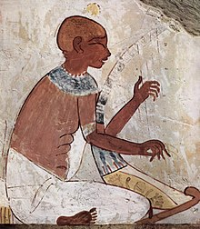 A brown-skinned man in white-linen garb, seated and playing a stringed harp with both hands