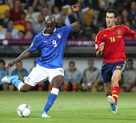 Spain holding midfielder Sergio Busquets (16, red) moves to block a shot from Mario Balotelli. Mario Balotelli shot Euro 2012 final 02 cropped.jpg
