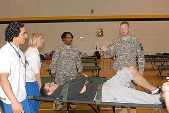 Maryland Defense Force - A Maryland National Guardsman and a Maryland State Guardsman teach nursing students proper evacuation procedures at Towson University.