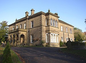 A stone house in two storeys, with an entrance portico and a two-storey bay window