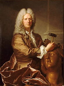A portrait of sculptor Nicolas Coustou in full grey wig, his expression with a slight smile, and holding a hammer, with which he is working on the head of a large bronze female figure
