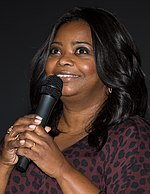 Profile of an African American female with black hair is talking through a microphone.