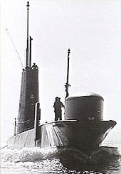 A submarine underway on the surface. A man is standing near the boat's bow sonar dome, while other personnel are visible on top of the sail