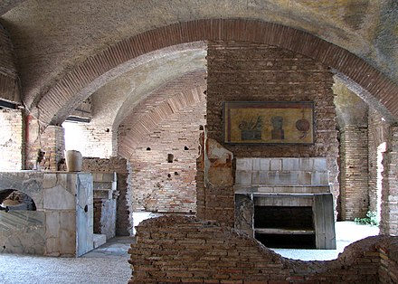 An Ostian taberna for eating and drinking; the faded painting over the counter pictured eggs, olives, fruit and radishes. Ostia antica-13.jpg