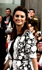 A blurry image of a smiling female with her hair clipped behind her head. She is wearing a black and white outfit that has sleeves that come up to her elbows. Behind her, people can be seen sitting and standing.