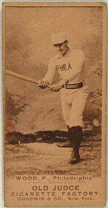 A sepia-toned baseball card image of a man wearing an old-style white baseball uniform and pillbox cap holding a baseball bat extended with both hands