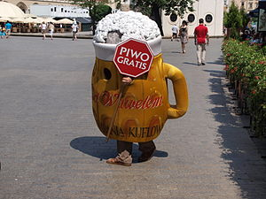 "Gratis versus libre - An advertising mascot dressed as a mug of beer, holding a sign saying ""Piwo gratis"" (Polish for ""free beer"") in the centre of Kraków, Poland, advertising beer being given away without charge."