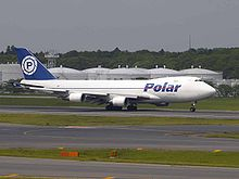 A white four-engine jumbo jet with a blue Polar logo, rolling out on an airport runway.