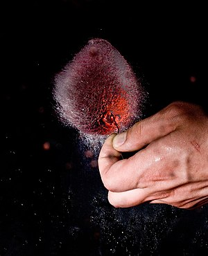 Popping a red water balloon.