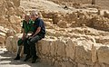 President George W. Bush and Prime Minister Ehud Olmert sit on a wall as they take a break from their tour of Masada.jpg