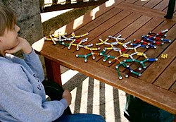 Seated boy facing 3/4 away from camera, looking at a ball-and-stick model of a molecular structure. The model is made of colored magnets and steel balls.