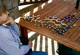 一個半背對鏡頭的男孩,注視著由球體與棍棒組成的分子結構模型。模型是以彩色磁鐵和鋼球構成。