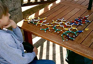 Restricted interests or repetitive behaviors, such as this boy's interest in playing with a toy model of molecules, may be features of Asperger's.