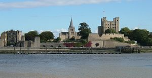 Rochester Castle - Rochester Cathedral is visible beyond the castle's ruined fortifications.