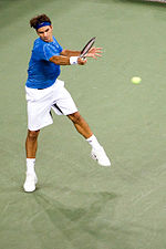 A brown-haired male tennis player with white shorts, a blue shirt and a blue headband swings a right-handed forehand on a hard court surface