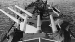 Een weergave van de voorwaartse kanonnen van een groot slagschip.  Er zijn twee torentjes van elk drie kanonnen.  De voorste toren is naar bakboord gedraaid, terwijl de achterste toren recht vooruit is gericht.