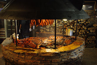 Barbecue restaurant - Several types of meats being cooked in a pit at a barbecue restaurant