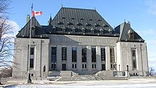 Large grey building in winter, with a Canadian flag in front