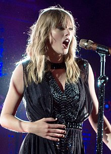 A photograph of Taylor Swift, as she looks towards from the camera, performing live with a mic attached to a piano.