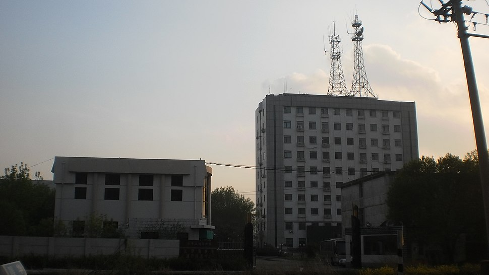 Two counter-lit buildings, the taller one has a large antenna on top