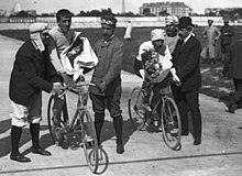 Two men with flowers in their hands, sitting on bicycles being held by other men, with the Eiffel tower seen in the background.