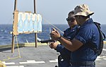 U.S. Navy Gunner's Mate 3rd Class Antonio Sanchez, front, gives Fire Controlman 3rd Class Ashley Cruz instructions on proper handling of the M9 Beretta pistol during small-arms qualifications June 10, 2013 130610-N-QL471-1103.jpg