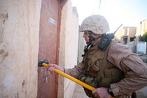 3rd Battalion, 14th Marines - A Marine with Battery M, 3/14 hammers a door during a cache search in Rutbah, Iraq.