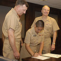 US Navy 040722-N-9693M-005 Chief of Navy Chaplains, Rear Adm. Louis V. Iasiello, left, watches with Commander, Naval Reserve Force, Vice Adm. John Cotton as newly commissioned Ensign Jeanette Gracie Shin signs her Oath of Offic.jpg
