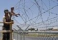 US Navy 040723-N-5821W-016 Seabees assigned to Naval Mobile Construction Battalion Seven Four (NMCB 74), install concertina wire on a fence line aboard the naval station.jpg