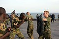 US Navy 051103-M-2175L-200 U.S. Marine Corps Lance Cpl. Ryan Papa, right, assigned to 2nd Platoon, Company C, 1st Battalion, 8th Marine Regiment, holds a striking pad for a member of the Senegalese 90th Naval Infantry.jpg