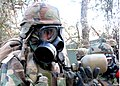 US Navy 070821-N-8547M-017 Builder 3rd Class James W. Strait, of Naval Mobile Construction Battalion (NMCB) 5, drinks through his protective mask during a chemical, biological and radiological protection drill in field exercise.jpg