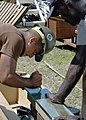 US Navy 070823-N-9195K-061 A local volunteer assists Construction Electrician 3rd Class Serafin Avila, attached to Naval Mobile Construction Battalion (NMCB) 7, as he cuts panes of glass that will be used as window slats.jpg
