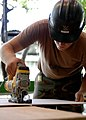 US Navy 070906-N-6278K-135 Equipment Operator 3rd Class Nathan Harper, a Seabee assigned to Construction Battalion Maintenance Unit (CBMU) 202, saws a board to reface cabinets for a laboratory at a local health training center.jpg