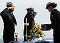 US Navy 090405-N-9950J-038 Aviation Maintenance Administrationman 3rd Class Fred Banks salutes as Aviation Machinist's Mate Tiffany Roach prepares to present cremains to Capt. Brent Canady during a burial at sea ceremony.jpg