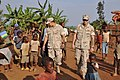 US Navy 090804-N-4928M-117 Hospital Corpsman 2nd Class Porfirio Nino and Boatswain Mate 2nd Class Mark St. Clair, assigned to Maritime Civil Affairs Team (MCAT) 104, tour a small village in Rwanda's eastern province.jpg