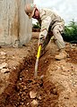 US Navy 100428-N-8936G-043 Builder 2nd Class Michael Moore digs a pipe ditch from the pump house to a new water distribution pad during construction in Naghad.jpg