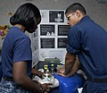 US Navy 111021-N-KA046-006 Hospital Corpsman 2nd Class Miguel Hernandez, right, demonstrates the correct CPR technique for Seaman Destiny Walker du.jpg